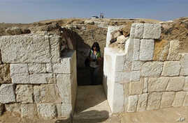 A journalist walks through the entrance of the newly discovered tomb of Rudj Ka, a priest who headed the mortuary cult of the pharaoh Khafra, near the Giza Pyramids in Cairo, Egypt, 19 Oct 2010