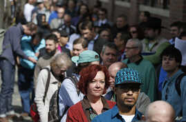Job seekers line up in the hundreds to attend a marijuana industry job fair hosted by Open Vape, in Downtown Denver, March 27, 2014.