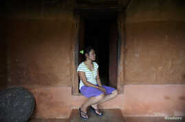 FILE - Stateless Nina Tamang, 18, is seen as she sits in the doorway of her red mud-stone hilltop home on the outskirts of Nepal's capital Katmandu, Aug. 14, 2011.
