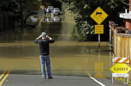 A man photographs a flooded street, Feb. 10, 2017, in Guerneville, Calif. The Russian River rose above its flood stage again Friday. More rain is forecast for the weekend.