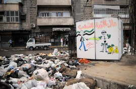 """Trash is piled high in the streets of Aleppo where collection stopped long ago. The sign reads, """"The money of the revolution is for the people,"""" November 10, 2012. (AP)"""