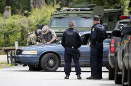 Law enforcement officers gather at an area of a possible sighting of two escaped prisoners from Clinton Correctional Facility in Dannemora, on June 23, 2015, in Mountain View, N.Y.
