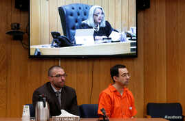 Defendant Larry Nassar (R) and his defense attorney Matt Newburg listen to Judge Janice Cunningham hand down his prison sentence during the sentencing hearing of Nassar, a former team USA Gymnastics, in the Eaton County Court in Charlotte, Michigan, ...