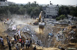 Palestinians gather as a bulldozer searches for victims amongst the rubble of a house, which police said was destroyed in an Israeli air strike, in Khan Younis in the southern Gaza Strip, July 21, 2014.