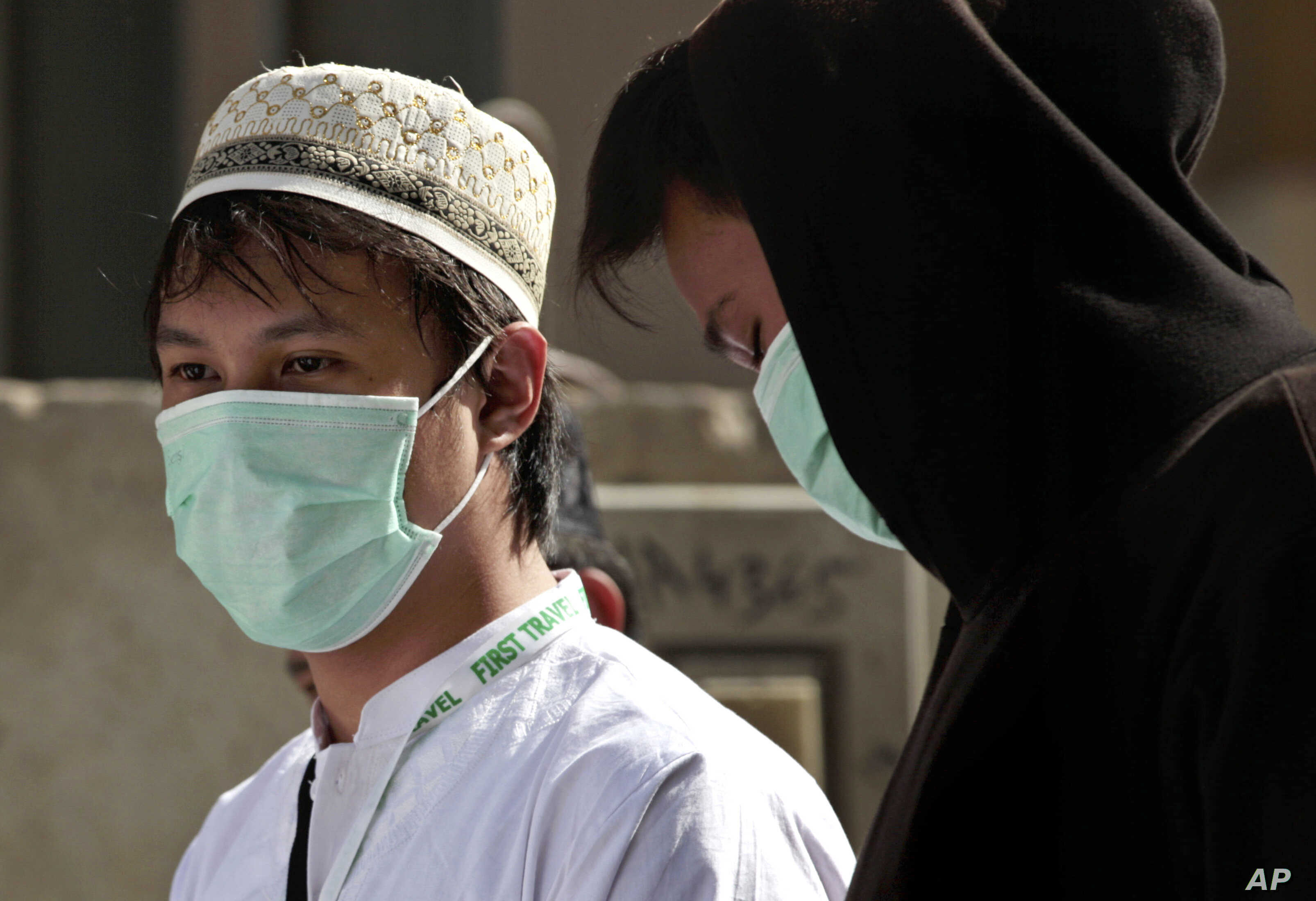 FILE - Muslim pilgrims wear surgical masks to help prevent infection from the MERS respiratory virus in Mecca, Saudi Arabia, May 13, 2014.