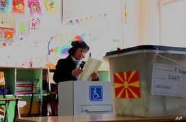 A woman looks at her ballot during general elections in Skopje, Macedonia, Dec.11, 2016.