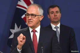 Australian Prime Minister Malcolm Turnbull speaks as Australia's Minister for Justice Michael Keenan listens on during a media conference in Sydney, Australia, July 30, 2017.