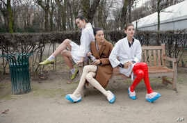 FILE - Models take a rest backstage after the Christian Dior's Spring-Summer 2015 Haute Couture fashion collection presented in Paris, Jan. 26 2015. Two of France's biggest luxury conglomerates, LVMH and Kering, have joined forces to establish a char