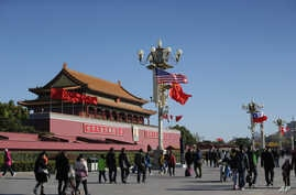 A U.S. flag is displayed beside a Chinese flag as tourists flock outside the Forbidden City in Beijing, Nov. 12, 2014.