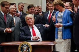 President Donald Trump, gives the pen he used to sign an Executive Order to Sen. Lisa Murkowski, R-Alaska, right, in the Roosevelt Room of the White House in Washington, April 28, 2017. The Executive Order directs the Interior Department to begin rev...