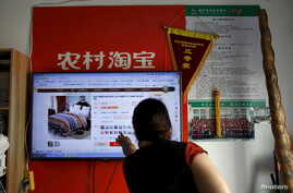 A customer points at a screen displaying a website of Alibaba's Taobao at a rural service center in Yuzhao Village, Tonglu, Zhejiang province, China, July 20, 2015.