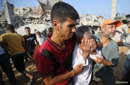 A Palestinian man reacts as people search for victims under the rubble of a house, which witnesses said was destroyed in an Israeli air strike, in Rafah in the southern Gaza Strip, July 29, 2014.