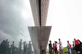 Visitors are reflected as they enter the Smithsonian National Museum of African American History and Cultural on the National Mall in Washington, May 1, 2017.