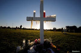 Candle drippings hang off one of 17 crosses at a memorial for the victims of the shooting at Marjory Stoneman Douglas High School in Parkland, Florida, Feb. 16, 2018.