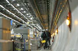 Technicians ride bikes in the tunnel of the Large Hadron Collider (LHC) experiment during a media visit at the European Organization for Nuclear Research (CERN) in Meyrin near Geneva, Switzerland on February 16, 2016.