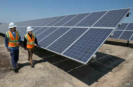 FILE - Employees walk past solar panels at a plant in Dixon, California, Aug. 17, 2017.
