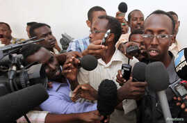 Somali journalist Abdiaziz Abdinur (R) talks to reporters after the high court freed him in the capital of Mogadishu, March 17, 2013.