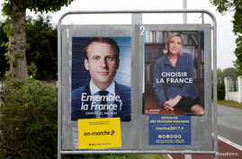 Official posters of the candidates for the 2017 French presidential election, Emmanuel Macron of the political movement En Marche! (Onwards!), left, and Marine Le Pen of the French National Front political party, are displayed in Saint-Josse, norther