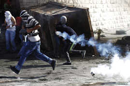 Palestinian youths run from tear gas canisters fired by Israeli border police during clashes at a checkpoint between the Shuafat refugee camp and Jerusalem, Nov. 7, 2014.