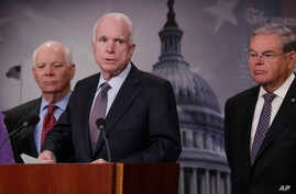 Senate Armed Services Committee Chairman Sen. John McCain, R-Ariz., flanked by Sen. Ben Cardin, D-Md., left, and Sen. Bob Menendez, D-N.J., speaks during a news conference on Capitol Hill, Jan. 10, 2017, to announce legislation lawmakers are introduc