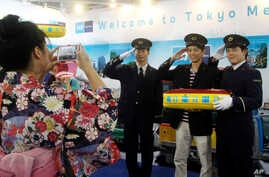 FILE - A Taiwanese visitor poses with uniformed employees of Tokyo Metro Co. for a souvenir photo at the booth of the Tokyo subway company at the Taipei International Travel Fair in Taipei, Taiwan, Nov. 8, 2014.