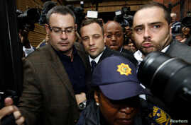 Olympic and Paralympic track star Oscar Pistorius (C) leaves after his trial at the North Gauteng High Court in Pretoria, South Africa, March 4, 2014.