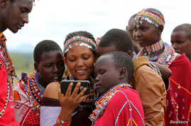 FILE - Maasai girls and a man watch a video on a mobile phone prior to the start of a social event advocating against harmful practices such as female genital mutilation at the Imbirikani Girls High School in Imbirikani, Kenya, April 21, 2016.