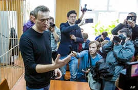 Russian opposition leader Alexei Navalny, foreground,  speaks to press in a court room in Moscow, Russia, March 27, 2017.