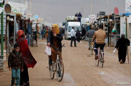 FILE - Syrian refugees ride bicycles during rainy weather at the Zaatari refugee camp in the Jordanian city of Mafraq, near the border with Syria, Dec. 18, 2016.