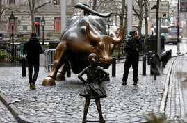 A camera man films a statue of a girl facing the Wall St. Bull, as part of a campaign by U.S. fund manager State Street to push companies to put women on their boards, in the financial district in New York, U.S., March 7, 2017.
