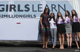 US First Lady Michelle Obama poses with young female students in front of the White House in Washington, DC, on March 8, 2016 before an event to mark International Women's Day.