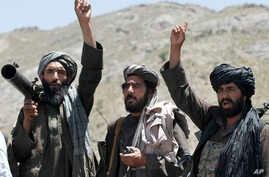 FILE - In this May 27, 2016, photo, Taliban fighters react to a speech by their senior leader in the Shindand district of Herat province, Afghanistan.