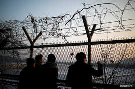 People look toward the north through a barbed-wire fence near the militarized zone separating the two Koreas, in Paju, South Korea, Dec. 21, 2017.