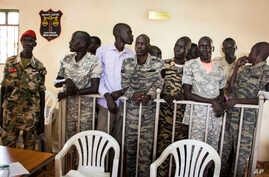 FILE - South Sudanese soldiers listen to the guilty verdict being delivered, Sept. 6, 2018, at their trial for rape and murder in a violent rampage in 2016 at a Juba hotel.