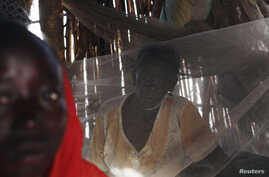 FILE - A Sudanese woman suffering from malaria sits inside her makeshift house in Golo, Fashoda county in Upper Nile State May 29, 2014.