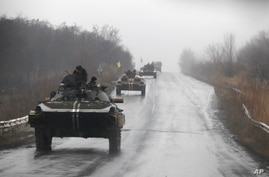 Ukranian military vehicles are seen driving on the road towards the town of Artemivsk, Ukraine, Sunday, Feb. 1, 2015.