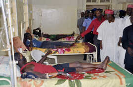 Government officials visit injured people from Tuesday's suicide bomb explosion, in a local hospital in Kano, Nigeria, Feb. 25, 2015.