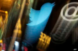 FILE -The Twitter logo appears on a phone post on the floor of the New York Stock Exchange.