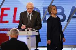 Democratic presidential candidate, Hillary Clinton enters the stage after a break as Democratic presidential candidate, Sen. Bernie Sanders, I-Vt,  makes notes, during the Univision, Washington Post Democratic presidential debate at Miami-Dade Colleg
