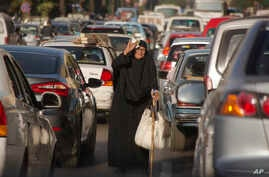 FILE -- An Egyptian vendor looks for clients amid a traffic jam in Cairo, Nov. 7, 2016. Social media, TV stations and newspapers in Egypt are abuzz after reports that the country's parliament speaker and his two deputies are using state funds to get