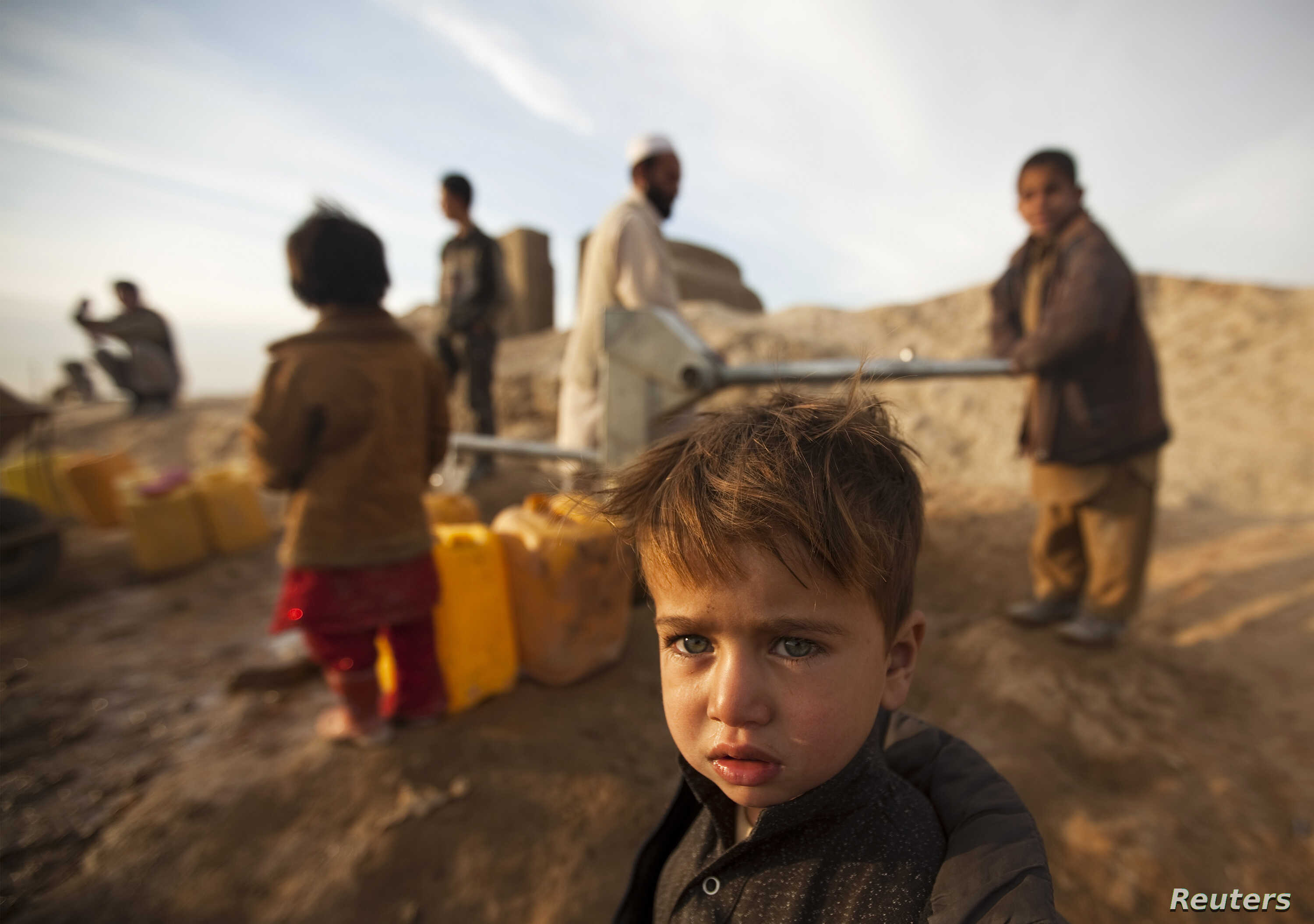 An Afghan boy stands near a public water pump in Kabul January 13, 2010. Nearly half way through the Afghan winter, unusually warm and dry weather is raising fears of a drought.