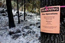 FILE - A notice warns visitors of controlled-fire operations in Kings Canyon National Park, Calif., Oct. 30, 2017.