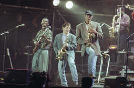 FILE - In this Aug. 16, 1991 file photo, Paul Simon, center, plays a finale with lead guitarist Ray Phiri, left, and actor-comedian Chevy Chase on the saxophone in New York's Central Park. Ray Phiri, a South African jazz musician who founded the band