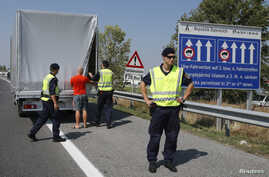 FILE - Austrian police officers control cars arriving to Austria at a checkpoint in the village of Nickelsdorf, Aug. 31, 2015.
