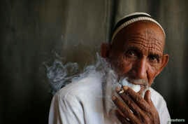 FILE - A man smokes a cigarette in the northern in the state of Uttar Pradesh, India, April 2014.