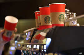 A barista reaches for a red paper cup as more, with cardboard liners already attached, line the top of an espresso machine at a Starbucks coffee shop in the Pike Place Market in Seattle, Nov. 10, 2015.