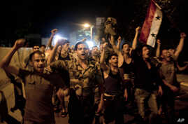 Sryian soldiers celebrate Bashar Assad's  presidential re-election in Damascus, Syria, Wednesday, June  4, 2014.