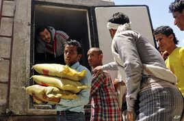 A Yemeni volunteer carries bags of rice to displaced people, who fled fighting in the southern city of Aden, during a food distribution effort in Taiz, Yemen, May 9, 2015.