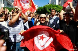 Anti-government protesters wave Tunisian flags as they rally for the dissolution of the Islamist-led government in Sfax, southeast of Tunis, Sep. 26, 2013.