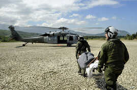 US Sailors assigned to Helicopter Sea Combat Squadron (HSC) 22 prepare to load an injured Haitian man onto an MH-60S Sea Hawk helicopter in Grand Goave, Haiti, Jan. 25, 2010